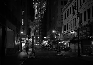 """Photo: """"Night in New York City...""""  At night after the multitudes have retreated to their homes away from the buildings and streets that hold them close during the day the city relaxes shaking the dust of the long day from its concrete limbs.  The street lights flicker like dream-heavy blinks of an eye while smokestacks exhale world-weary breaths of smoke into the yawning night air.    New York Photography: Financial District street at night with a smoke stack.    You can view this post along with information about where to purchase prints of this image at my site here:  http://nythroughthelens.com/post/37720947843/new-york-city-at-night-financial-district-street  -  Tags: #photography  #newyorkcity  #newyorkcityphotography  #nyc  #nycphotography  #manhattan  #night  #nightphotography  #newyorknight  #nycnight  #citynight  #city  #cityphotography  #urban  #urbanphotography  #street  #streetphotography  #blackandwhitenewyorkcityphotography  #noir  #noiretblanc  #noirnyc  #newyorknoir  #citynoir  #blackandwhite  #blackandwhitephotography  #smoke  #poetry  #prose"""