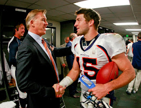 Photo: Elway congratulates Tebow in the locker room after the victory. Photo by Eric Lars Bakke / Denver Broncos