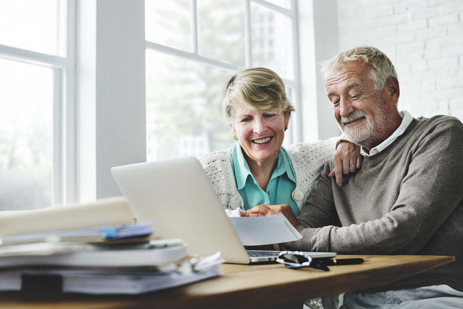 CEF stock: Senior couple smiling while looking at their checks