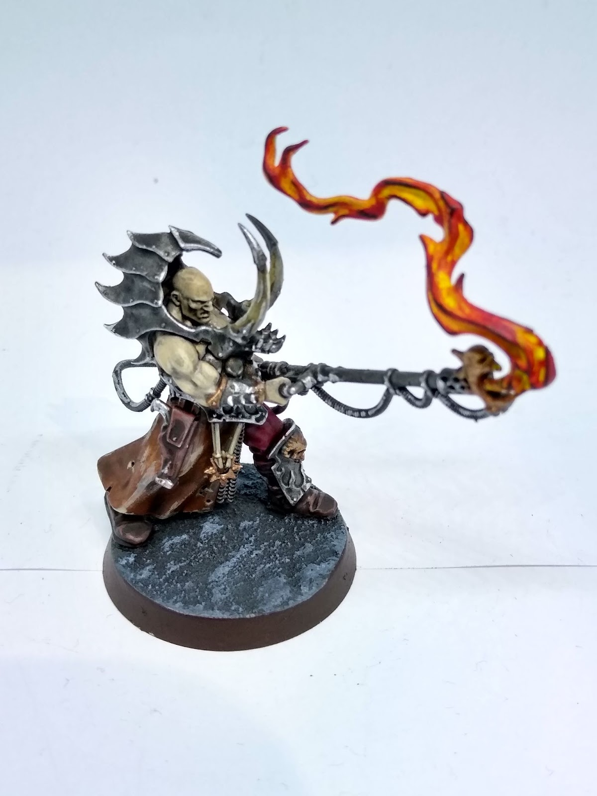 A cultist firebrand model - a burly man in horned armour, wielding a flamethrower with a daemonic face.