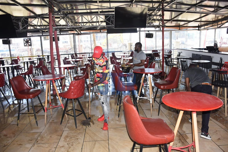 Aerias Mwirori a chef at Blend Bar and Restaurant cleans the floor in preparation of the reopening of bars on September 29,2020.