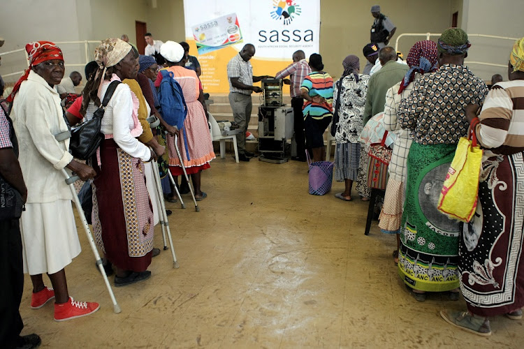 Pensioners queue to collect their grants at a Sassa pay point. File image