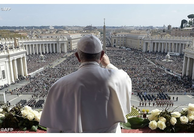 Pope Francis blessing the crowds from the central loggia of St Peter's Basilica following the Easter Day Mass last year - AFP