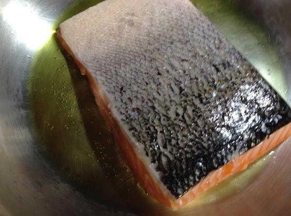 Lightly salt the fresh salmon on the flesh side. Heat olive oil in a...