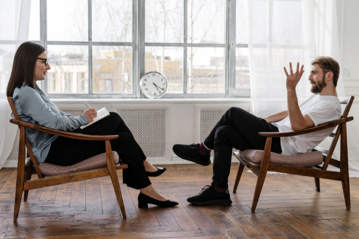 Therapist sits with man
