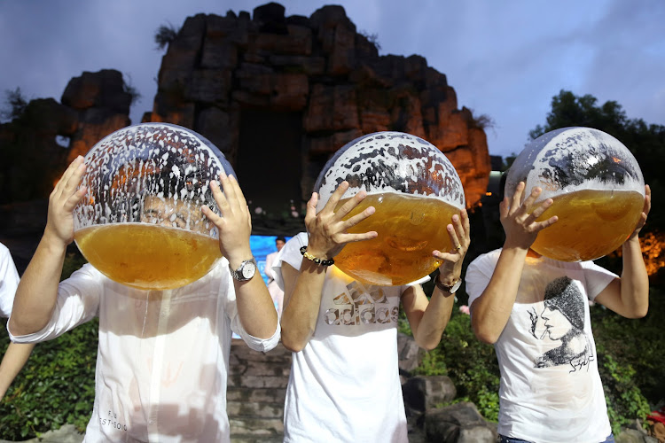 People drink from fish bowls at a beer-drinking competition in Hangzhou, China.