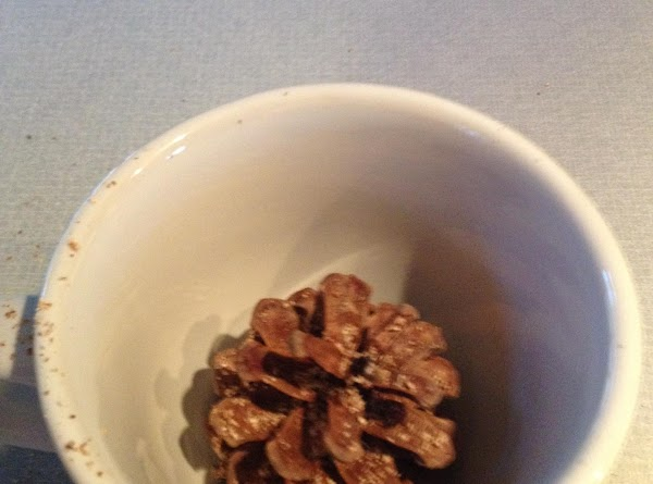 Spray pine cone with spray glue, then put it into the cup/mug.