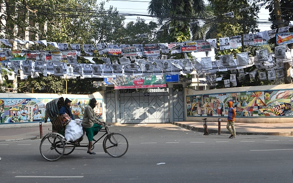 A rickshaw driver cycles past a street adorned with election posters in Dhaka on December 28 2018, ahead of the December 30 general election. Picture: GETTY IMAGES/ AFP/ INDRANIL MUKHERJEE