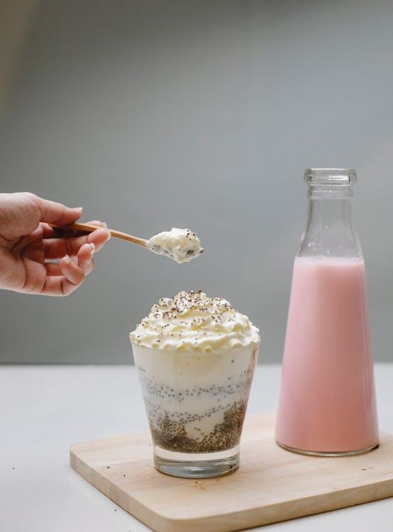 Women checking dessert with whipped cream