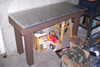 Photo: It's time for insulation and drywall! However, before we get to that, I wanted to show off my finished workbench/table. I finally got around to painting the table and was able to complete the top over the weekend. I used galvanized sheet metal to cover the wood, and then laid a second layer of flashing over that. I also finished the edges of the table with 90° angle metal strips to cover any sharp edges from the sheet metal and flashing.