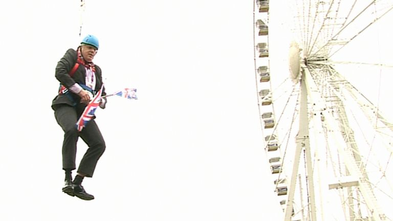 London Mayor Boris Johnson as he is left hanging in mid-air after he got stuck on a zipwire at an Olympic event at Victoria Park in the capital. 2012