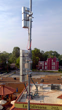 """Photo: A Nanostation M5 and Nanostation M2 Loco hung on a mast fashioned from 1/2"""" EMT conduit, with improvised shielding.  Note the hose clamps holding the radios to the mast."""