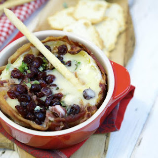 Bacon-wrapped baked Brie with port wine cranberry sauce.