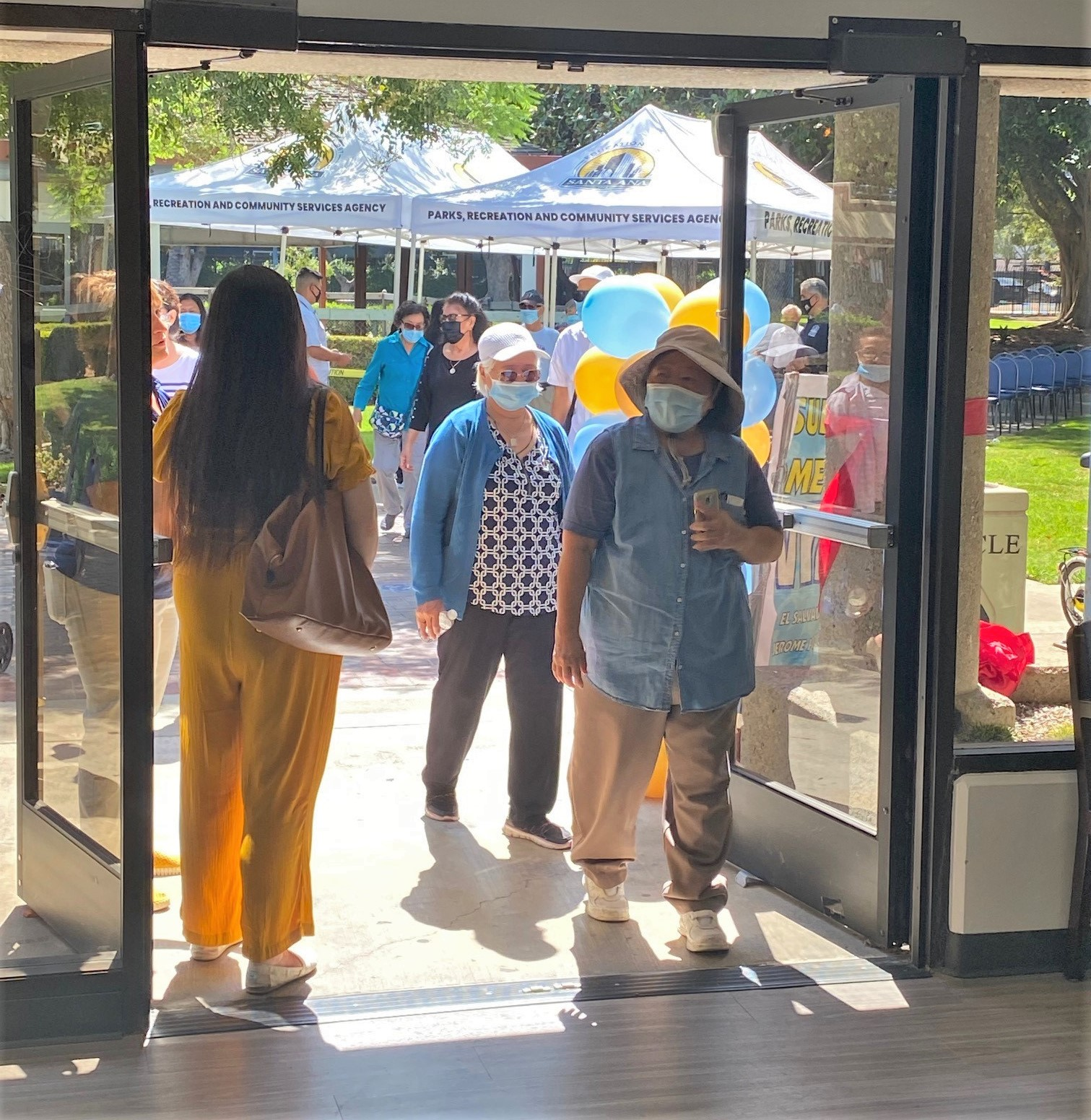 An image of two elderly ladies walking into the Santa Ana senior center. The one in front has smiling eyes, and both ladies are wearing masks.