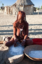 Photo: Himba village - Himba woman making corn flour / Vesnice Himbů - Himba žena drtí kukuřici na mouku