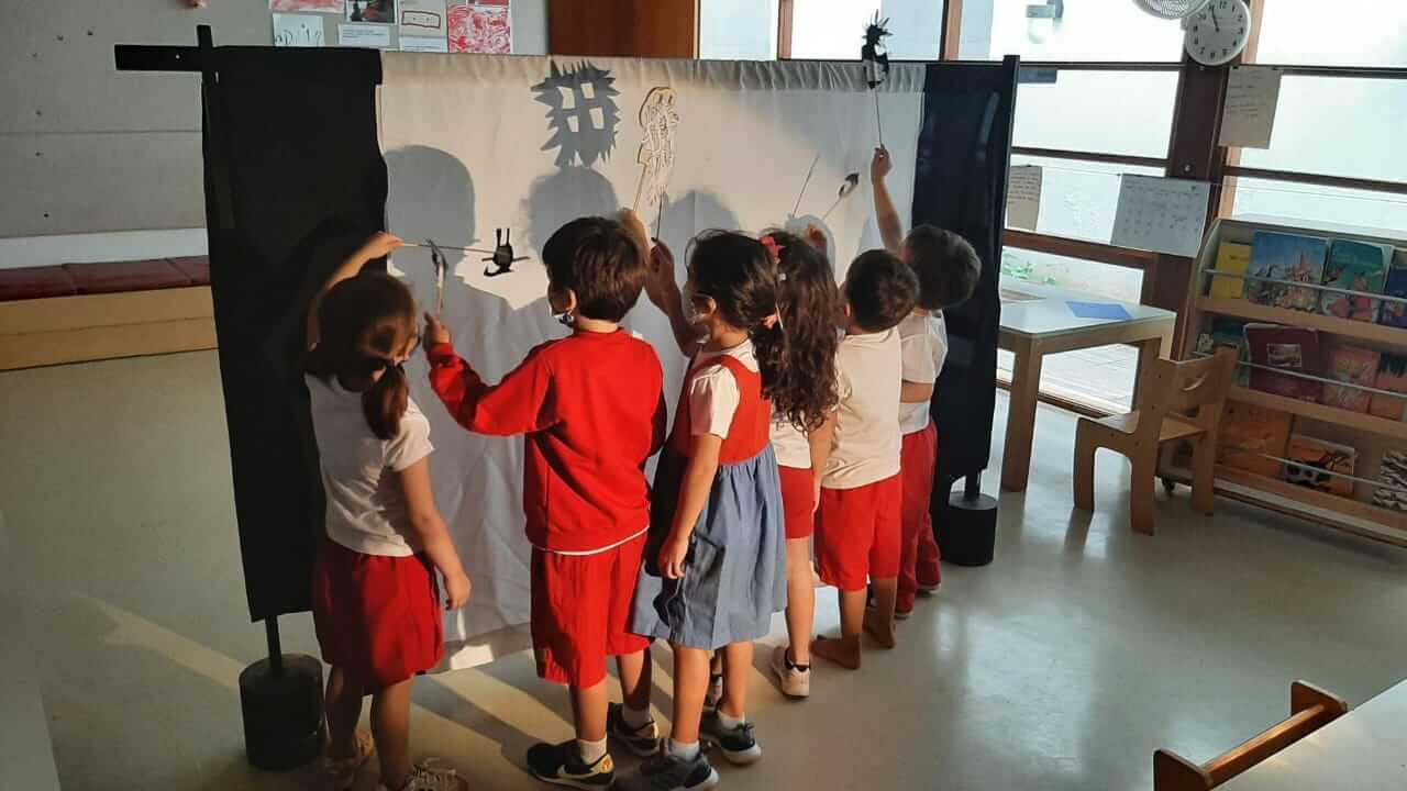 A imagem mostra várias crianças interagindo em um teatro de sombras.
