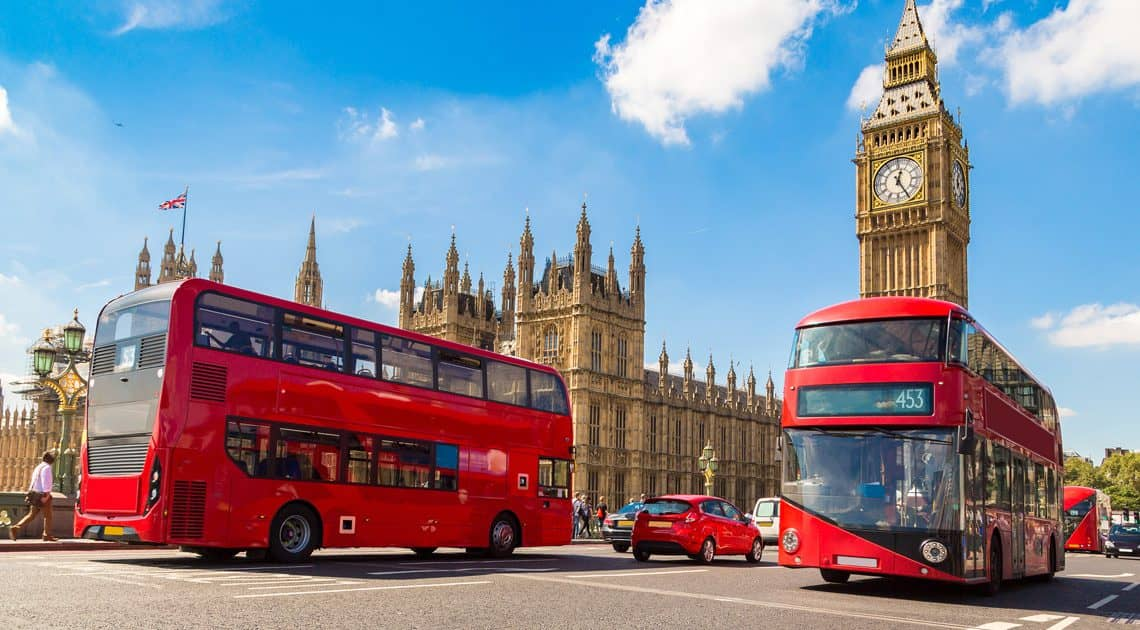 Two double-decker buses in front of Big Ben in London.