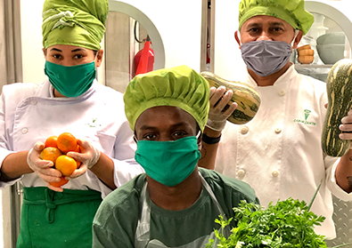 Three chefs in masks and white robes are holding up fresh produce for the camera.