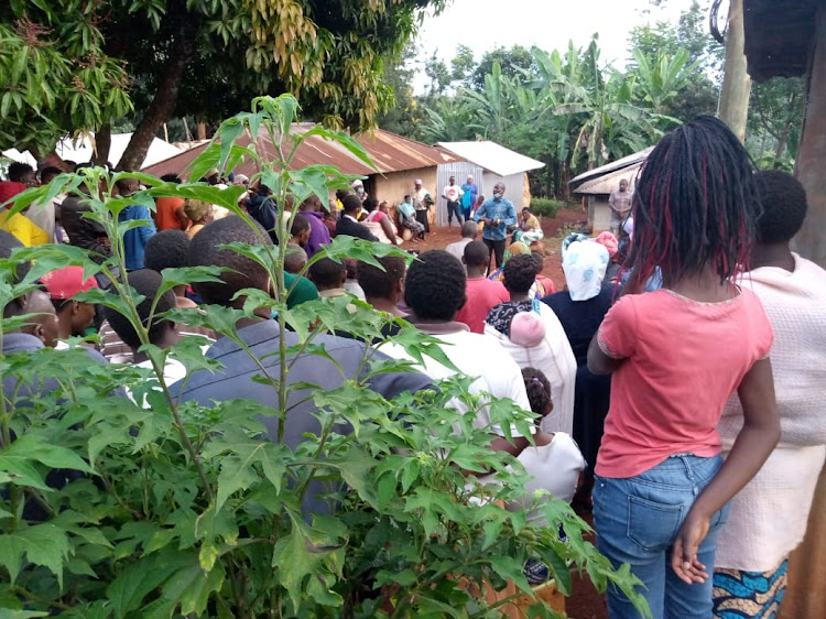 Gakuyu residents gather at a home where two children died in a fire.