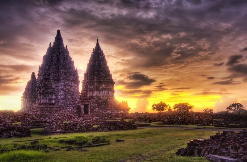 Photo: Prambanan Sunset   You can imagine what it was like to find this amazing temple in the hot, steamy jungles of Indonesia.  The day had been very stormy, so I spent that time exploring the temple while getting soaked... quietly hoping that the storm clouds would break on the horizon to allow the sun through.  Sometimes the lighting is best right after the sunset.   And sometimes this is right when the police come to get you.  Maybe they were security guards.  But it was hard to tell in the dark - and, besides, I didn't know the difference between the clothes of a security guards and a policeman in Indonesia.  I had Will with me when these guys approached us, and he was no help at all.  He did manage to keep them busy for a while so I could take some final shots, but we could tell that we had worn out our welcome.  So then the guards started to escort us right out of there.   - from Trey Ratcliff at http://www.StuckInCustoms.com