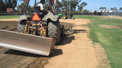 Photo: Also using this skip loader to dig out old infield mix along the basepath.
