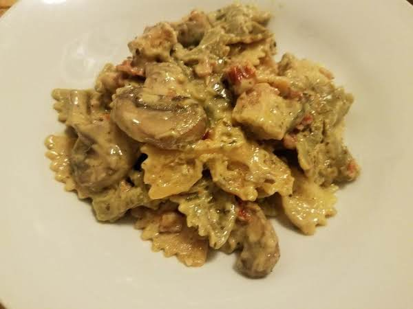 Decadent, Creamy Bowtie Pasta With Pesto, Sun-dried Tomatoes, Baby Portobello Mushrooms, And Grilled Chicken. Yum!