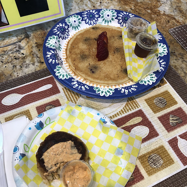 Partially consumed gf crab cake with gf remoulade. Gf pancake with blueberries.