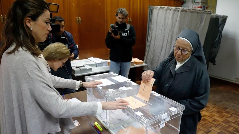 Una religiosa introduce la papeleta de voto al Senado en un colegio electoral