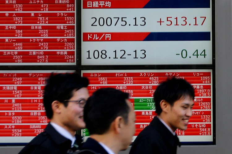 Pedestrians walk past an electronic board showing the Nikkei stock index outside a brokerage in Tokyo, Japan. Picture: REUTERS/KIM KYUNG-HOON