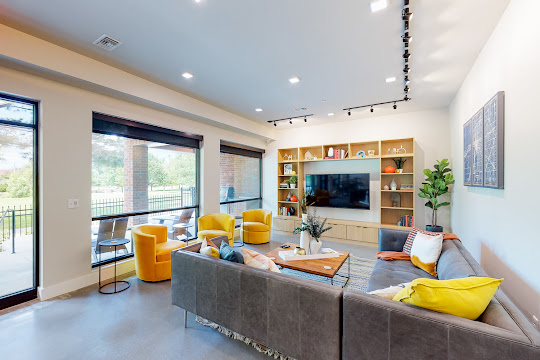 Community clubhouse with lounge seating, TV, and windows to see outdoor seating area