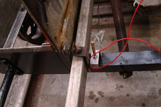 """Photo: Photo showing the left-rear rail bracket disassembly (Part logged/tagged as """"2010-Jan-27 #1"""").  Note spacer washers used. Perhaps a properly sized replacement bracket can be fabricated? The electrical switch to the right of the lift rail was the temporary brake light switch installed during the 2009 summer to meet NARCOA regulations. Photo by Jack Loucks."""