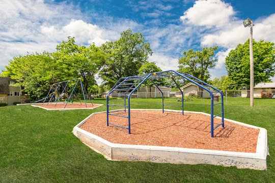 Playground with swings and slides, and jungle gym area around Elmwood Estates