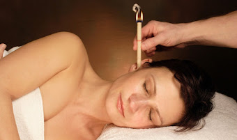 a lady lying down receiving ear candling treatment