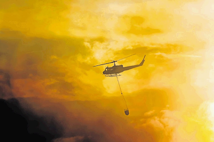 A helicopter over wildfires. Picture: HERALD