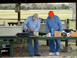 Photo: Bob Barnett working on his spray gun that is plugging up.  Bill Howe looking on.   2014-0104 RPW