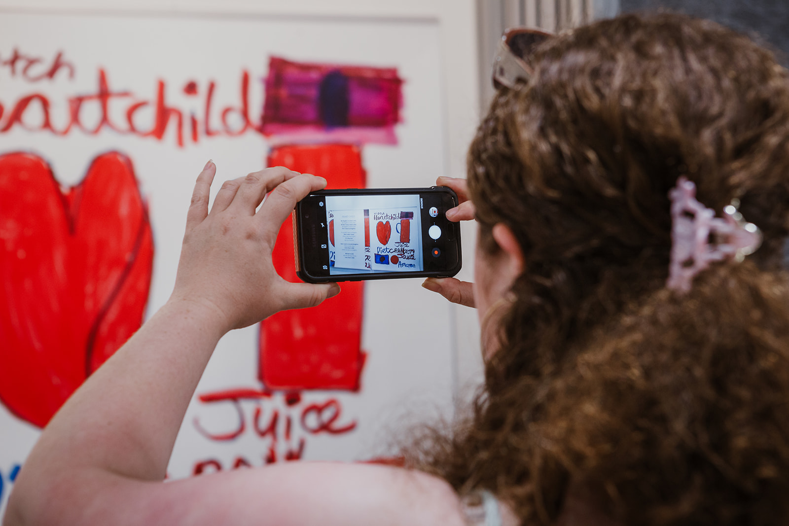 A visitor takes a Smartphone photo of Teresa's 'Heart Child' artwork at the opening of Born to Represent. Photo: This Is It Studios.
