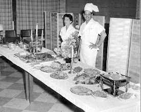 """Photo: Gilbert & Mary Garza, Chef and waitress at the Chase Field """"O"""" Club, stand by the food they've prepared for the going away party for Capt. G.H. Duffy on July 31, 1959"""