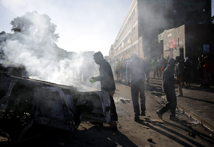 Smoke rises from a burning vehicle following a night of xenophobic violence in Johannesburg.  File Picture: EPA/KIM LUDBROOK