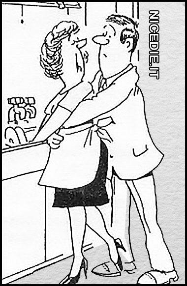 una donna con il grembiule sta cucinando, un uomo gli cinge i fianchi da dietro