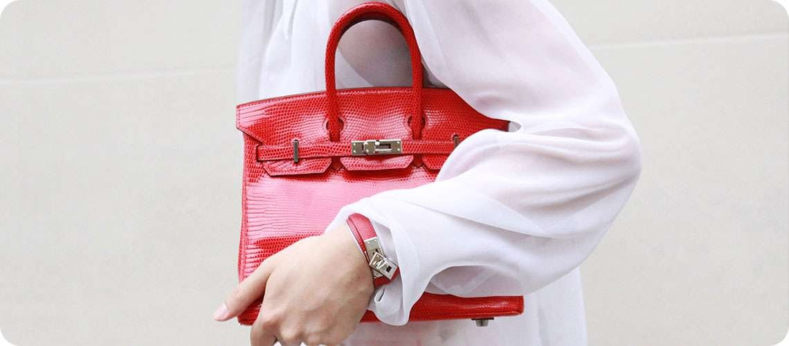 a lady in a white shirt holding a red handbag