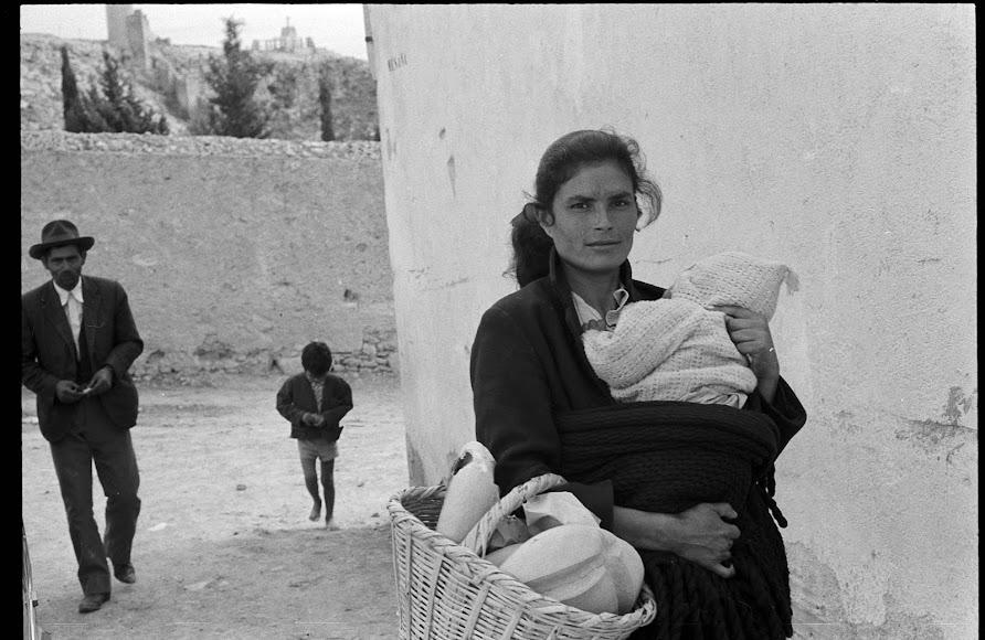 Una mujer sujeta a su bebé y carga enseres en un canasto. Le siguen lo que parece el resto de la familia.