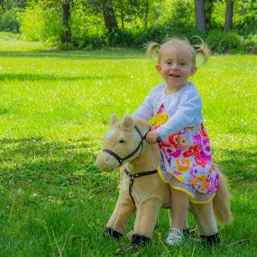 Riding in the Park by Scott Morgan - Babies & Children Child Portraits ( little girl, rocking, park, grass, rocking horse, dress, horse, little )