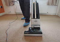 A man vacuuming a carpet from the front
