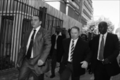 ON THE MARCH: The eighth state witness Aubrey Morris Shlugman (in striped tie) arrives at court to give evidence in the corruption case of former police commissioner Jackie Selebi yesterday. Pic: BAFANA MAHLANGU. 12/11/2009. © Sowetan.