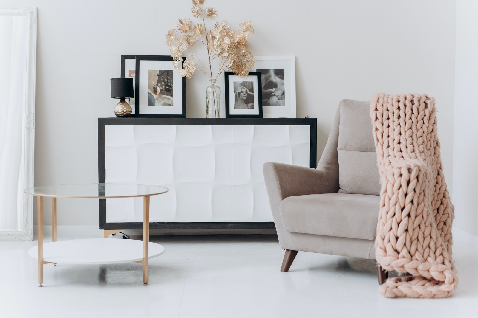 minimalist interior design with table and picture frames and a couch with pink knitted cloth of a condo unit space