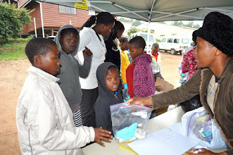 Photo: Ms. Zanele giving a hygiene pack to each child.