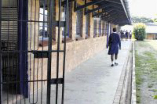 'SERIOUS ALLEGATIONS':A pupil walks towards a group of fellow pupils at Makhumbuza High School in Umlazi where five 'predator' teachers were suspended. 04/05/09. Pic. Thuli Dlamini. © Sowetan.