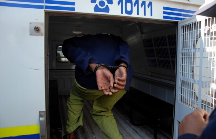 A man gets inside a police van after his appearance at the Court.