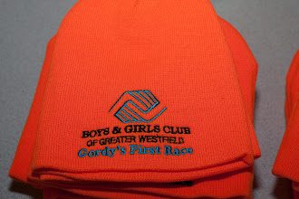 "Photo: Quote from Springfield Republican: GORDY GOING ORANGE: In honor of Gordon Bates, the second annual Gordon Bates First Race elected to hand out orange winter hats instead of the standard T-shirt to its runners. More than 80 people turned out for the New Year's Day race in Westfield, which had a 5K and 10K course.  ""Gordy was well known for wearing an orange hunting cap and used to wear it frequently to races he directed,"" race director Mike Sheldon said. ""So we decided that most runners already had enough T-shirts. His family was pleased with the choice."""
