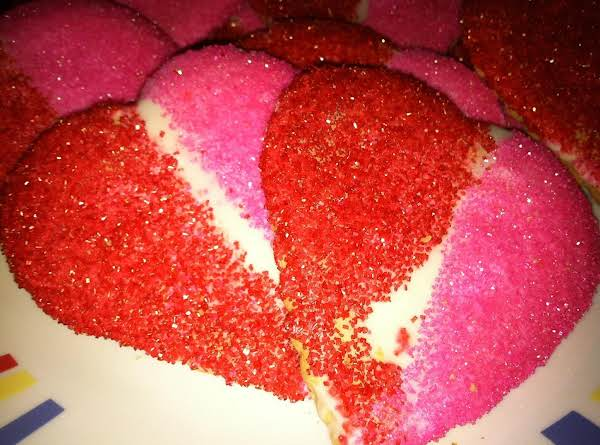 Pretty Pink And Red Sugars Sprinkled On Wet White Icing.